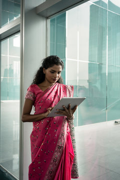 Portrait of young Indian woman using a tablet PC outdoors against the glass wall of a modern business building