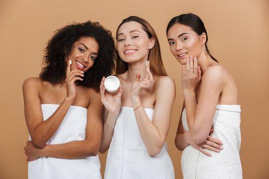 Beauty photo of three smiling multiracial women with different types of skin: caucasian, african american and asian girls, applying face cream together isolated over beige background