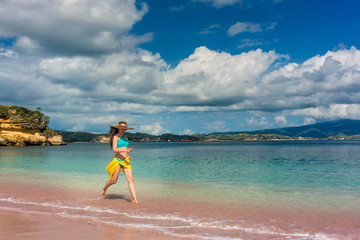 Full length of a fashionable young woman enjoying happiness and freedom while walking on a tropical beach during summer vacation in Komodo Island, Indonesia