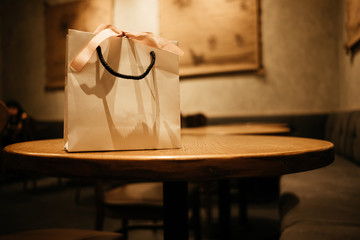 celebration paper bag with ribbon place on wood table in restaurant with copy space