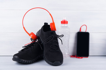 black sneakers and a mobile phone with red headphones, and a bottle of water, on a gray background