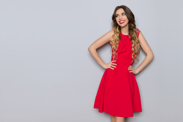 Smiling Young Woman In Elegant Red Dress Is Looking Away