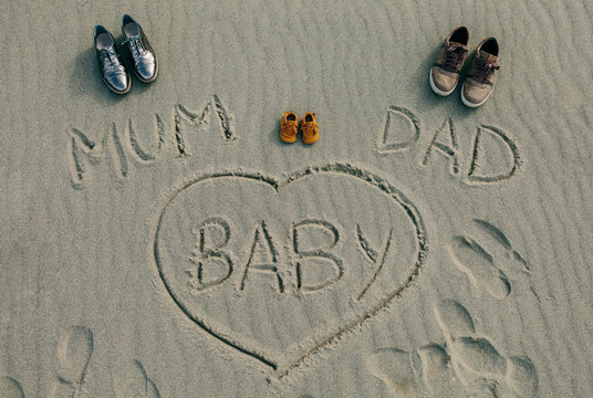 Mum, dad and baby written on the sand of the beach next to their shoes