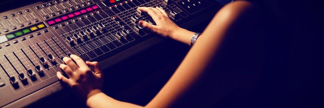 Female audio engineer using sound mixer