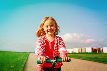 happy little girl riding scooter in summer