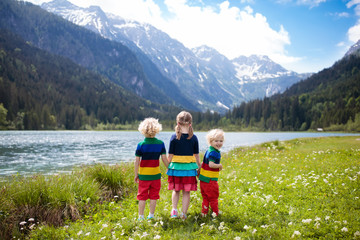 Children hiking in flower field at mountain lake