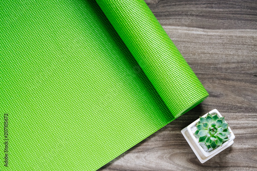986c41fdd222c Green yoga mat on a wooden background with green Succulent pant, Top View  with copy space. Active healthy relaxing lifestyle background concept.