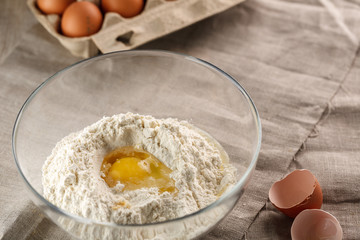 preparation of dough for flat bread. broken egg and flour in a glass bowl