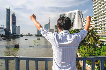 A  businessman is proud for the successful of company and his job. Hand up in the air and feeling powerful,happy, success and achievement concepts , City background.