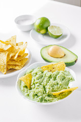 Latin American guacamole sauce with a snack of corn chips on a white table