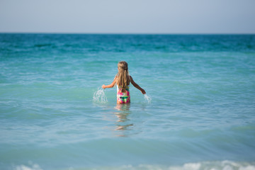 Little girl in the sea. A little girl enters the sea water, rear view.