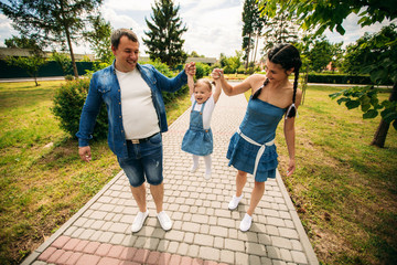 Happy joyful young family father, mother and little daughter having fun outdoors, playing together in summer park, countryside. Mom, Dad and kid laughing and hugging, enjoying nature outside
