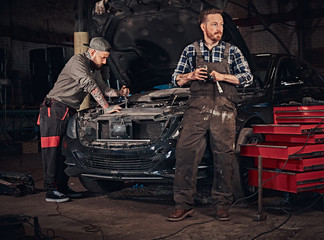 Two bearded auto mechanic in a uniform, repair a broken car in the garage.