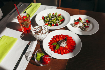 Rustic kitchen table with strawberry tiramisu, top view.  Italian food concept