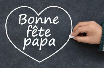 Main d'enfant écrivant bonne fête papa et dessinant un cœur à la craie sur une ardoise