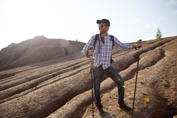 Photo of young tourist man in cap with walking sticks walking in mountainous area