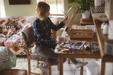 Female artist painting picture on canvas in living room