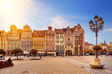 Central market square in Wroclaw Poland with old colourful houses, street lantern lamp and walking tourists people at gorgeous stunning morning sunrise sunshine. Travel vacation concept Wall mural