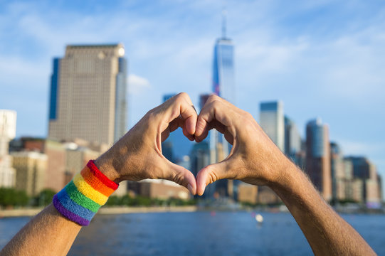 Hands wearing pride rainbow wristband making heart symbol
