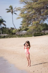 Girl clicking photo of sea with camera