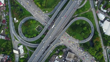 Fotobehang - 4K. Aerial view of infinity highway road interchange with busy urban traffic speeding on the road. Junction network of transportation in Bangkok, Thailand. taken by drone