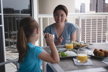 Mother and daughter having meal at home