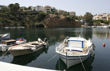 The white boats near the coast of the lake Voulismeni and the high cliff in the small mediterranean town in Greece on the sunny day