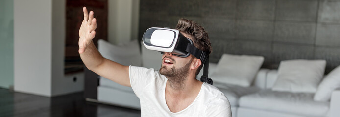 Young bearded man with VR glasses touching imaginary interface indoors