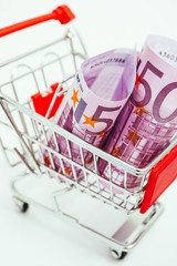 Poster Metal basket with an Euro 500 banknote in it. Consumption, shopping concept, pushcart.