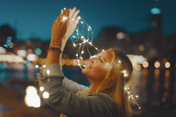 Happy young blonde woman with garland fairy lights have fun in city at night