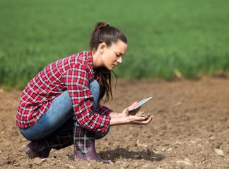 Farmer woman checking soil quality