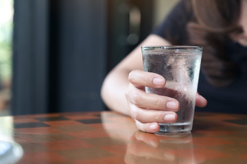 Closeup image of woman's hand holding a glass of cold water on table