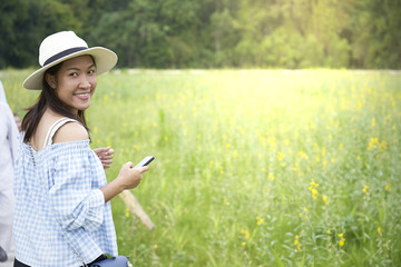Asian girl is using a smartphone to take photos in a flower garden.