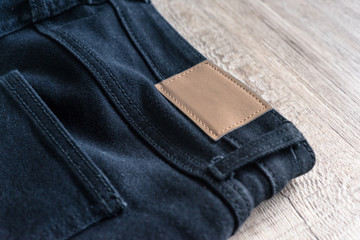 Back of jeans on wood background with leather label.