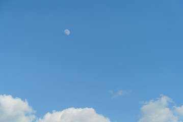 Moon during the day, blue sky with clouds