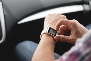 Man using smartwatch in a car