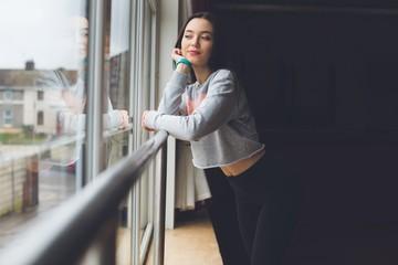 Female dancer looking through window in dance studio