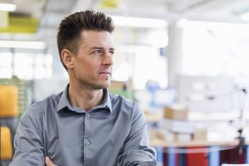 Portrait of confident man in factory looking sideways