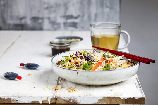 Salad with glass noodles, cabbage, carrots, bell peppers, spring onions, peanuts and hot Thai dressing