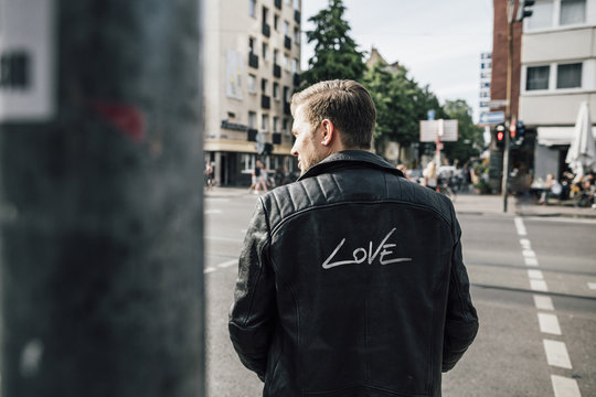 Back view of young man wearing black leather jacket with writing 'Love'
