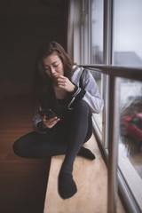 Female dancer using mobile phone in dance studio