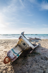 Abandoned broken wooden boat or pirogue with painted eye in front at beach on sunny day, Casamance, Senegal, Africa