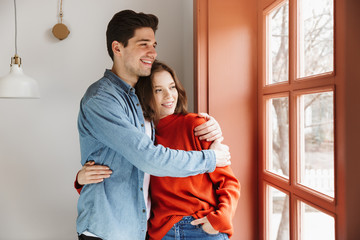 Lovely young couple hugging while standing
