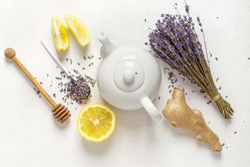 Lavender herbal tea in a white teapot, lemon and ginger