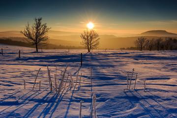 Sonnenuntergang im goldenen Sonnenlicht über dem winterlichen Erzgebirge. Blick zum Scheibenberg, Fichtelberg und Keilberg.