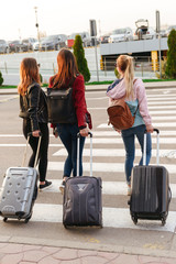 Portrait of three caucasian women from back traveling abroad together, carrying luggage to airport. Air travel or holiday concept