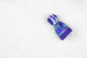 Purple wool hat/cap on the white snow with copy space. Top view.