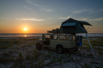 4x4 offroad vehicle with roof top tent camping on beach during sunset, Casamance, Senegal, Africa
