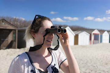 Woman by the seaside looking through binoculars