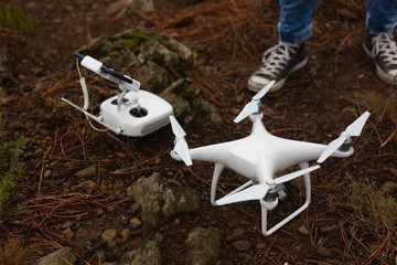 Man standing with flying drone and remote control